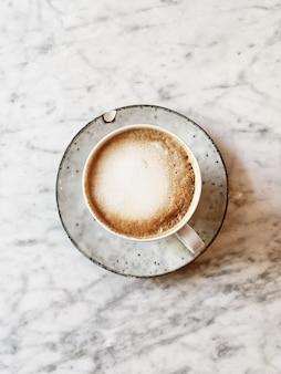 Une tasse de café ou de cappuccino avec plaque à la main posée sur une table en marbre