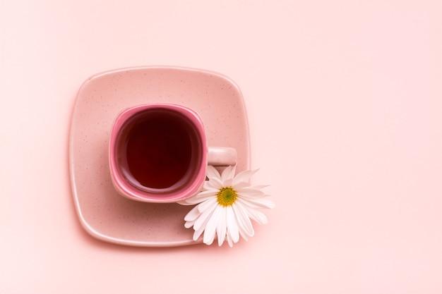 Tasse à café carrée avec boisson rose avec fleur sur soucoupe sur fond rose.