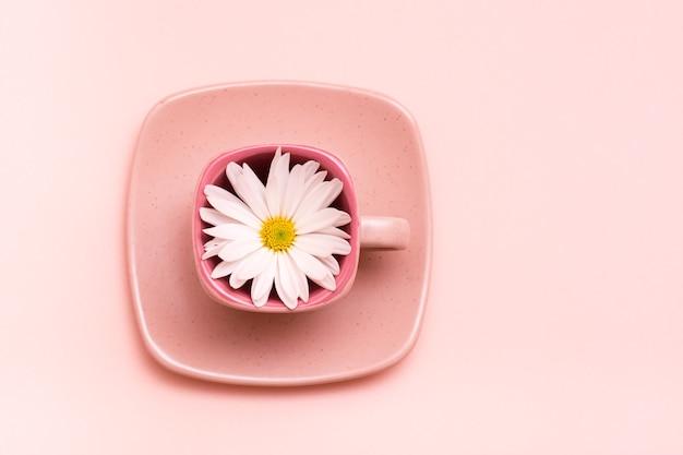Tasse à café carrée vide avec fleur sur soucoupe sur fond rose.