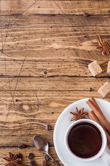 Tasse de café, cassonade et cannelle avec anis sur bois