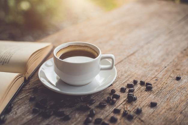 Tasse à café en céramique blanche d'americano chaud noir sur une table en bois