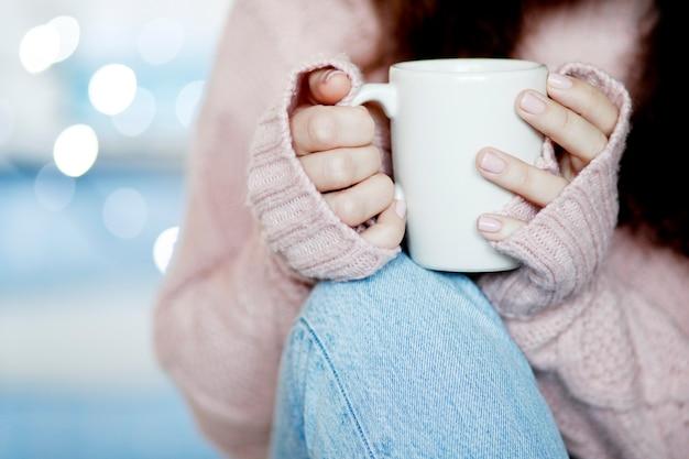 Tasse à café en céramique blanche dans la main de la femme
