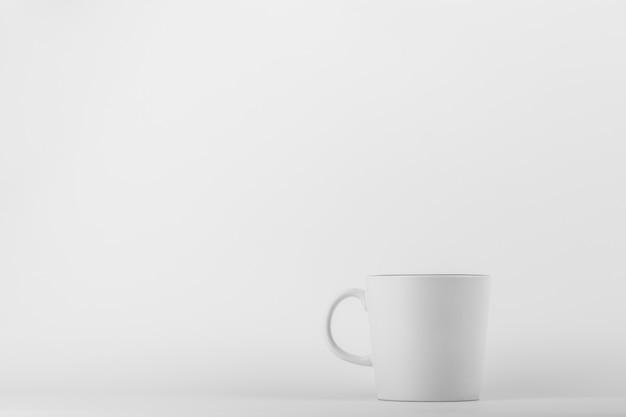Tasse à café en céramique blanche sur fond blanc.