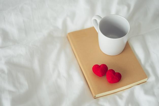 Tasse à café en céramique blanche posée sur la couverture marron du cahier et deux coeurs rouges.