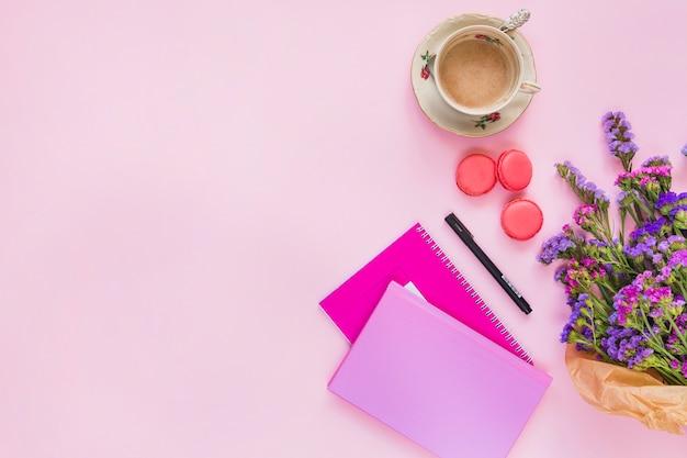 Tasse à café en céramique; macarons; stylo; carnet de notes et bouquet de fleurs sur fond rose