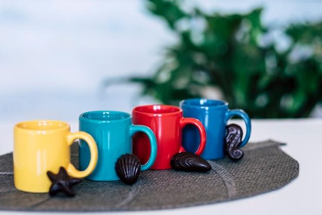 Tasse à café en céramique quadricolore avec table blanche de chocolats en forme de poisson et de coquillage