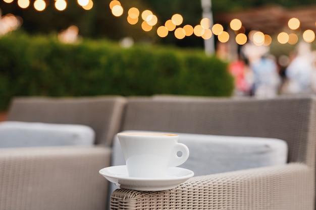 Une tasse de café sur une chaise dans un restaurant avec un arrière-plan sur les lumières de la guirlande