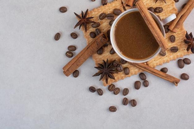 Une tasse de café chaud avec de l'anis étoilé et des bâtons de cannelle sur des craquelins. photo de haute qualité