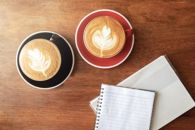 Tasse de café chaud avec art au latte en forme de feuille et livre vide.