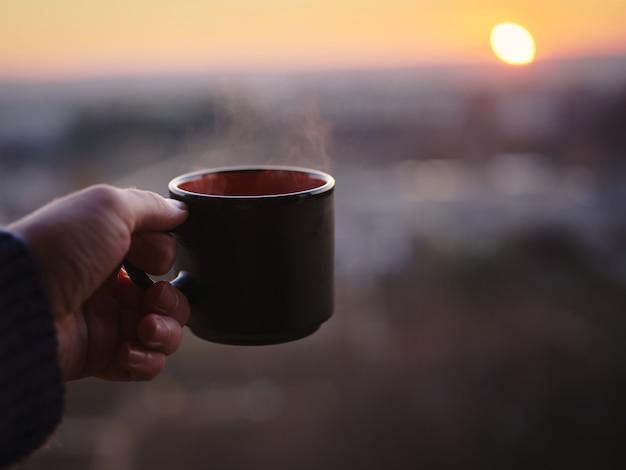 Tasse de café chaud au coucher du soleil