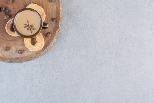Tasse de café chaud avec des bâtons de cannelle sur un morceau de bois.