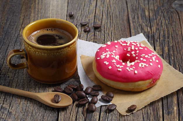 Tasse de café chaud et beignet aux fraises pour le petit déjeuner sur table en bois