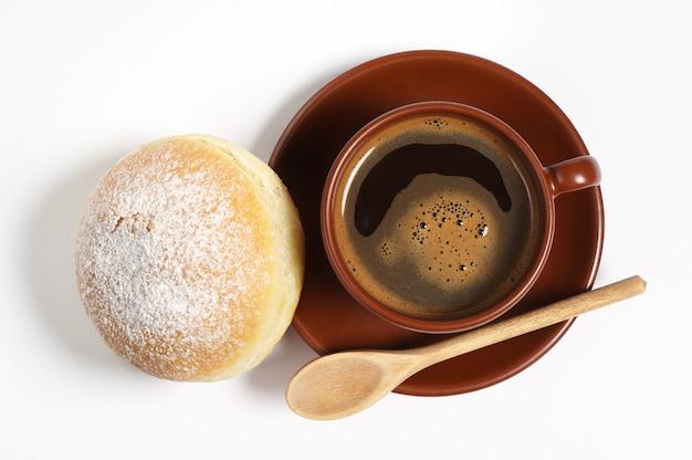 Tasse de café chaud avec beignet frais pour le petit déjeuner sur fond blanc, vue de dessus