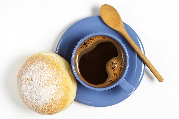 Tasse de café chaud avec beignet sucré pour le petit déjeuner sur fond blanc, vue de dessus