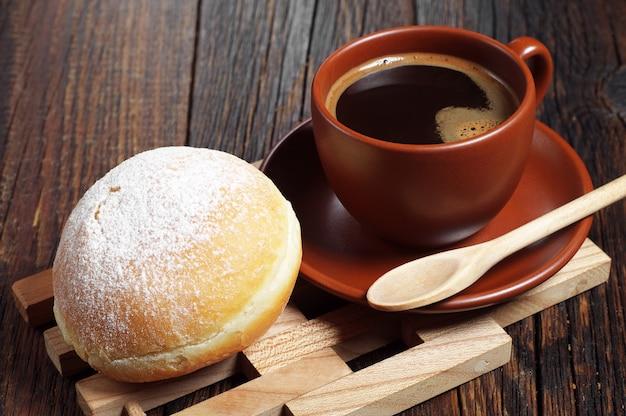 Tasse de café chaud avec beignet sucré pour le petit déjeuner sur table en bois
