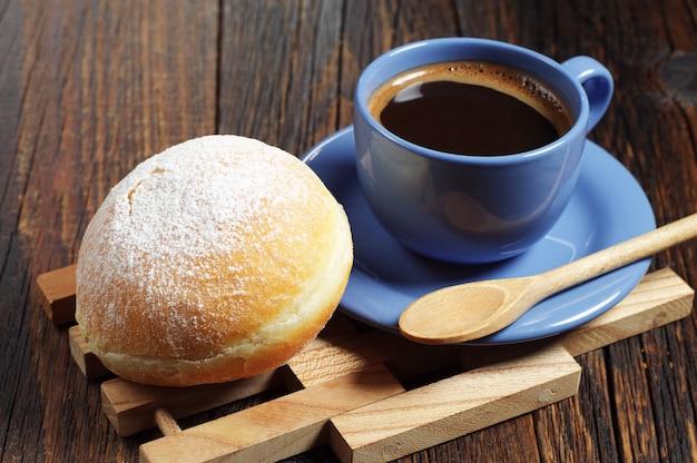 Tasse de café chaud avec beignet sucré pour le petit déjeuner sur une vieille table en bois