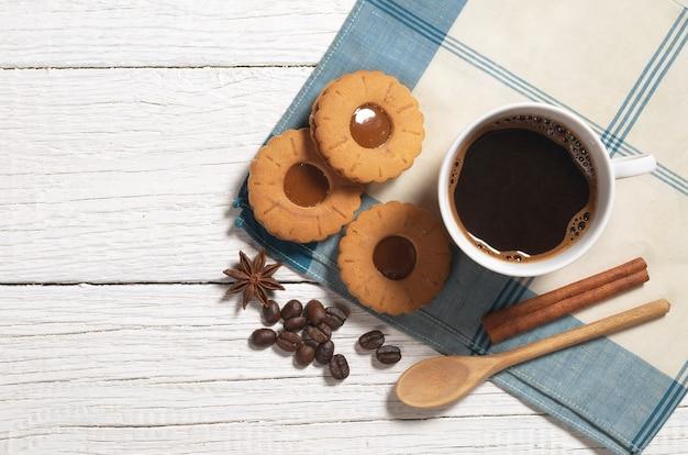 Tasse de café chaud et biscuit au caramel sur table en bois blanc, vue de dessus