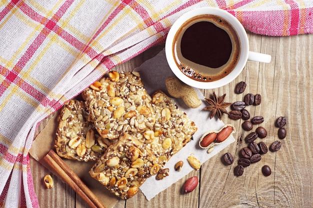 Tasse de café chaud et biscuits aux noix sur une nappe recouverte de table en bois, vue de dessus