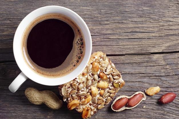 Tasse de café chaud et biscuits aux noix sur une table en bois foncé, vue de dessus