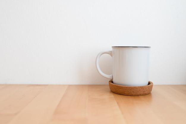 Tasse à café chaud blanc sur table en bois et mur blanc avec espace de copie.