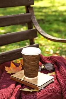 Tasse de café chaud avec chandail chaud et feuilles d'automne sur banc en bois dans le parc