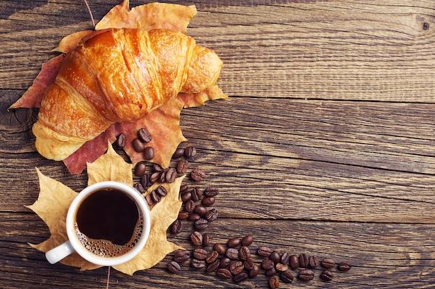 Tasse de café chaud, croissant et feuilles d'automne