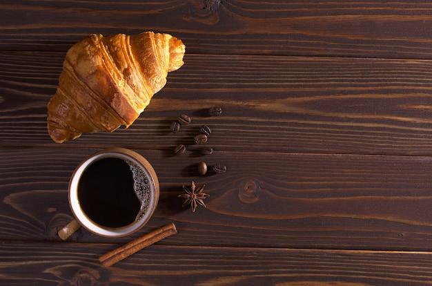 Tasse de café chaud et croissant pour le petit déjeuner sur une table en bois sombre