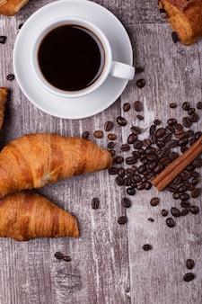 Tasse de café chaud et croissants fraîchement préparés sur une table en bois sombre. croissant savoureux.