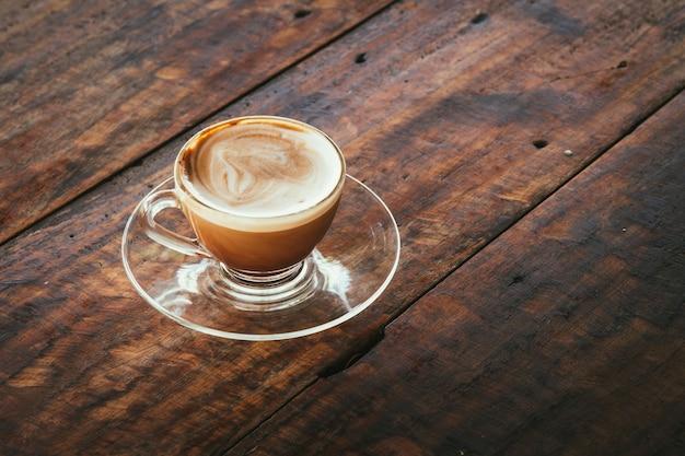 Une tasse de café chaud dans une tasse à café en verre sur une vieille table en bois