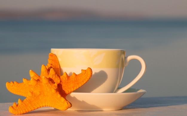 Tasse de café chaud du matin avec des étoiles de mer, bonjour.