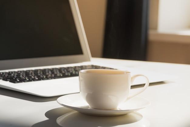 Tasse de café chaud du matin fumant et ordinateur portable
