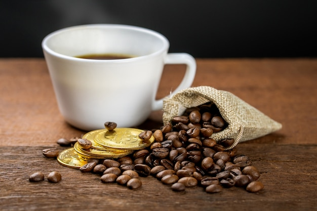 Une tasse de café chaud est sur une table en bois, décorée avec du grain de café et une pièce d'or. un café peut faire plus d'argent.