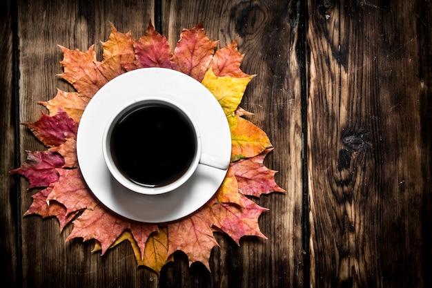 Tasse de café chaud avec des feuilles d'automne