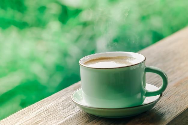 Tasse de café chaud sur fond vert naturel