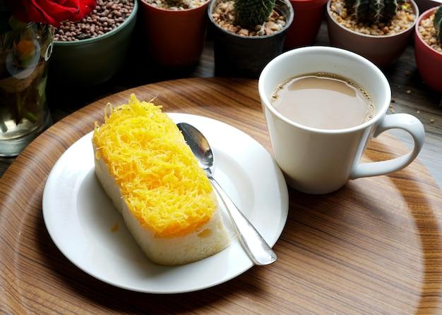 Une tasse de café chaud avec golden thread cake et fond de cactus