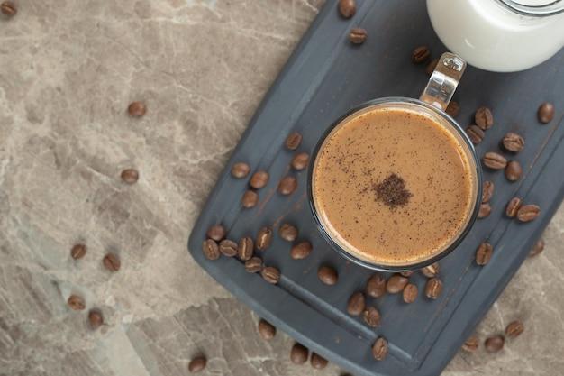 Tasse de café chaud et grains de café sur une assiette sombre.