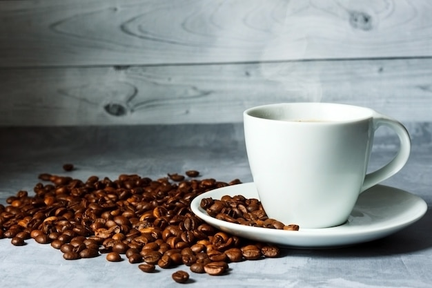 Tasse de café chaud et grains de café sur fond de bois clair