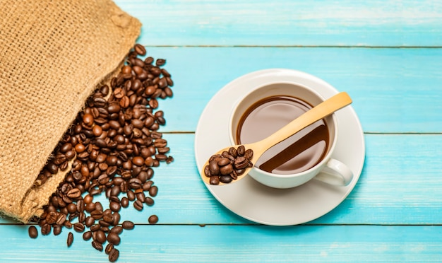 Tasse de café chaud et grains de café torréfiés du sac de voyage sur une table et une cuillère en bois.