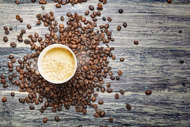 La tasse de café chaud avec des grains de café