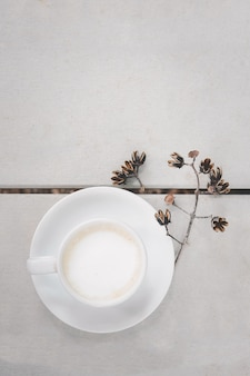Tasse de café chaud latte art sur plancher en bois fond de couleur blanche et fleur sèche, en vue de dessus.