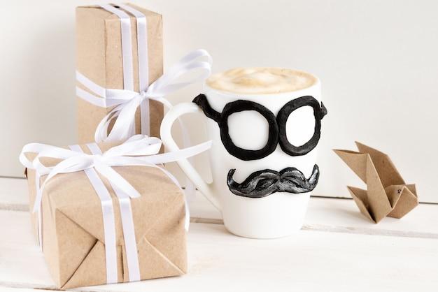 Une tasse de café chaud avec de la mousse et des cadeaux pour la fête des pères.