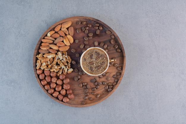 Tasse de café chaud mousseux et diverses noix sur une plaque en bois.