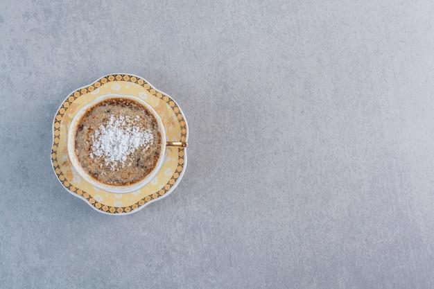 Tasse de café chaud mousseux placé sur une table en pierre.