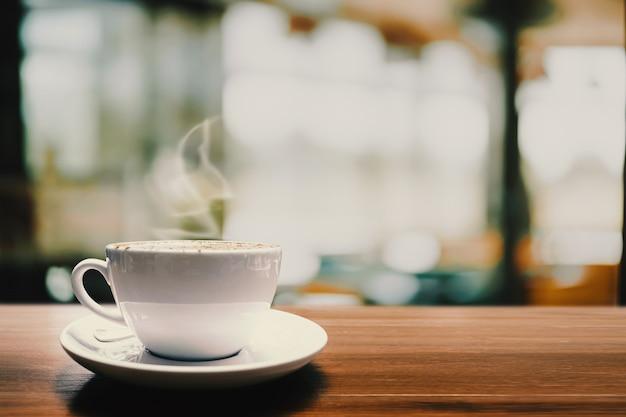 Tasse de café chaud sur la table en bois dans le café pour le fond.