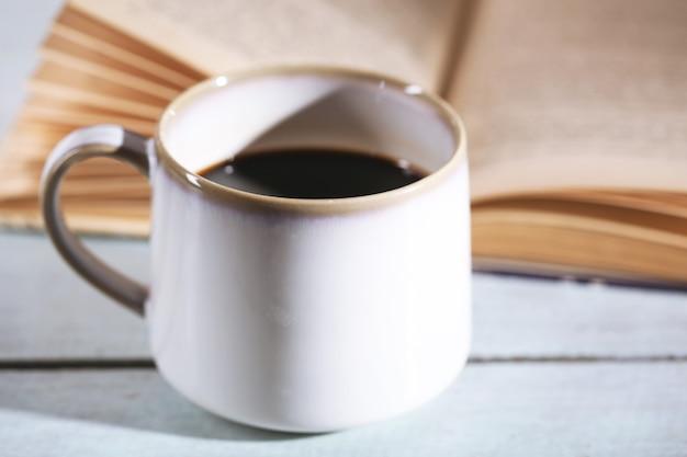 Tasse avec café chaud et vieux livre sur table en bois