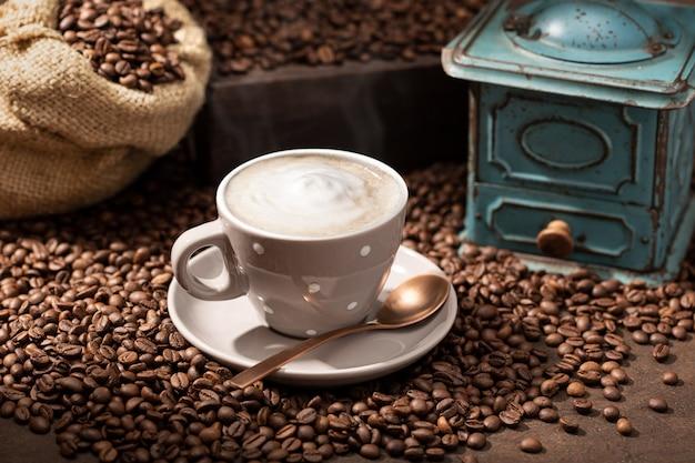 Tasse à café chaude cappuccino ou latte, haricots rôtis et vieux moulin. fond de café rustique