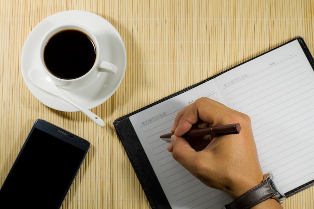 Tasse à café chaude avec carnet et mobile sur l'homme d'affaires de bureau