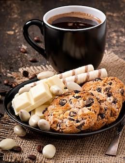 Tasse de café avec chocolat blanc, amandes et biscuits