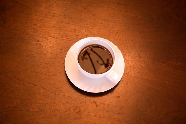 Une tasse de café classique sur un bureau en bois foncé.