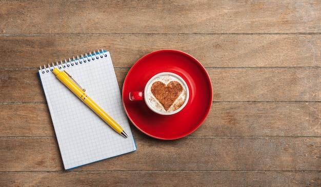 Tasse de café avec coeur de forme et note avec stylo sur une table en bois
